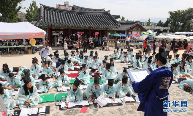 韓國萌娃穿儒生服體驗科舉考試 小蘿莉偷瞄同伴考卷(圖)